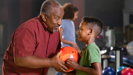 Grandfather showing his grandson how to bowl at a bowling alley.