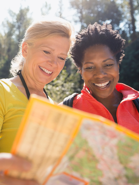 Women looking at trail map in sunny woods